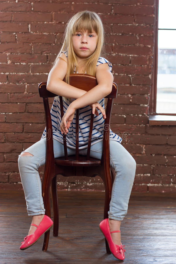 女孩在牛仔裤的6岁坐 免版税库存照片