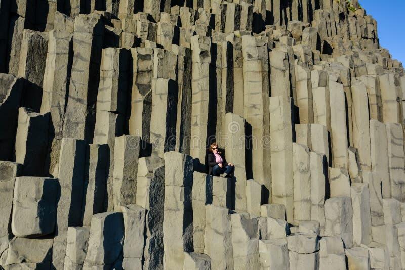 女孩在玄武岩石头专栏中部坐Reynisfjara 库存照片