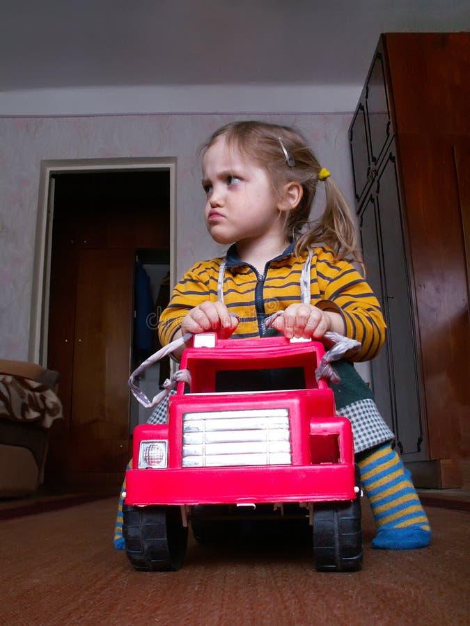女孩在玩具汽车坐并且做滑稽的面孔 免版税库存图片