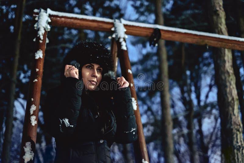 女孩在用雪盖的公园拿着敞篷毛皮 免版税库存照片