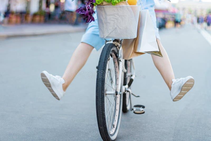 女孩在白色自行车的城市附近赶走 库存照片