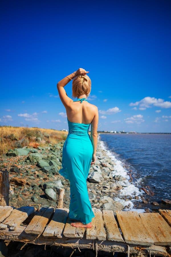 女孩在礼服的海滩和神色站立入距离 库存照片