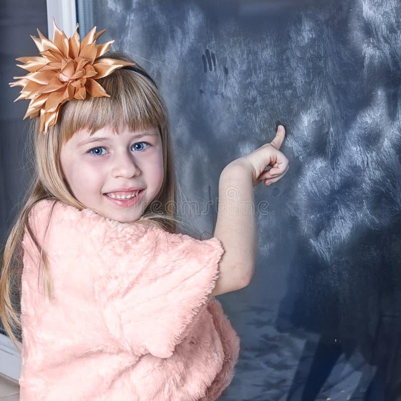 女孩在礼服的5岁在冬天窗口附近 免版税库存图片