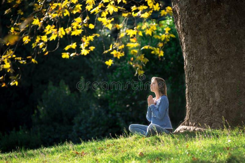 女孩在秋天思考坐草在一棵槭树下 免版税库存图片