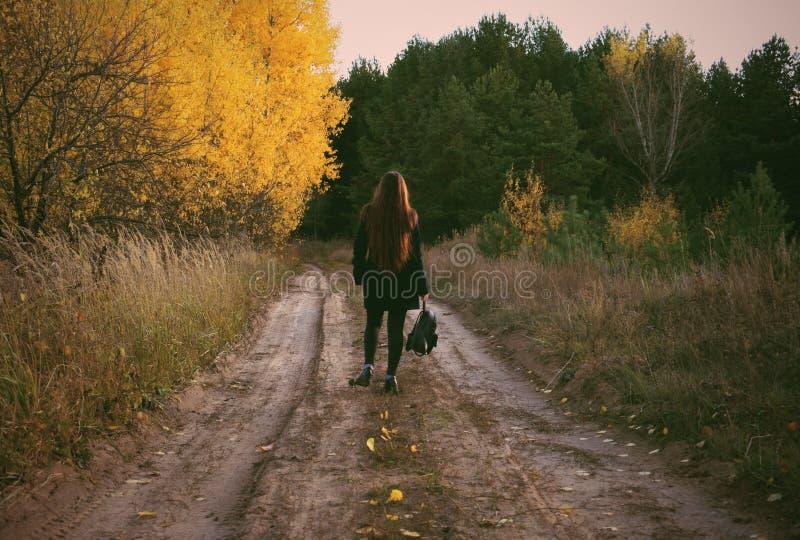 女孩在秋天森林里走 库存照片
