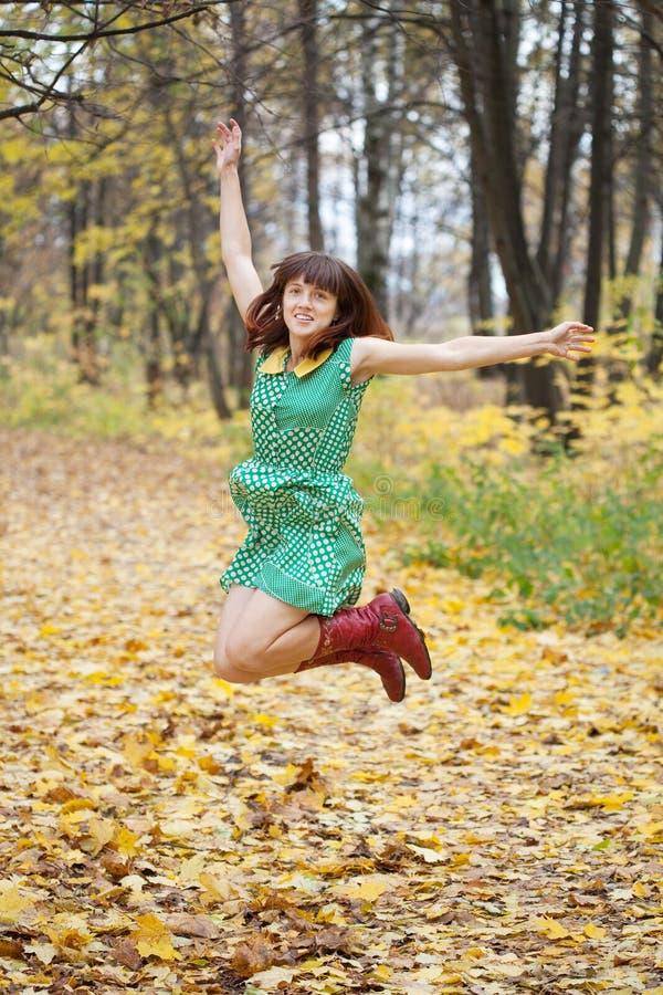 女孩在秋天跳 免版税库存图片