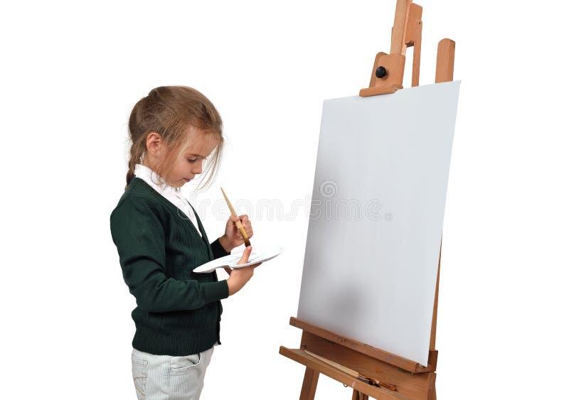 女孩在空白的画架绘 免版税库存照片