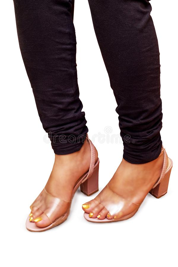 女孩在穿着黑暗的牛仔裤和透明桃红色凉鞋的城市 免版税库存照片