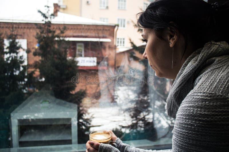女孩在窗口附近拿着一杯咖啡 免版税库存图片