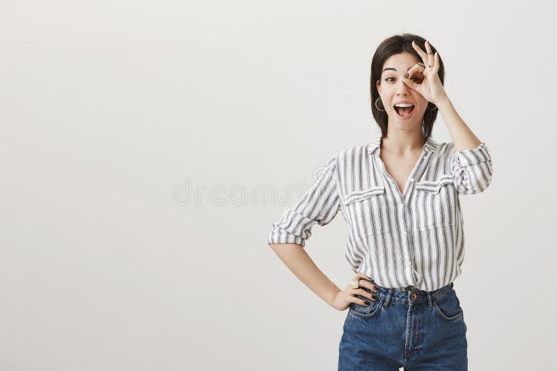 女孩在窥视孔假装她看 激动的愉快的年轻都市妇女室内画象时髦衣裳显示的 免版税图库摄影
