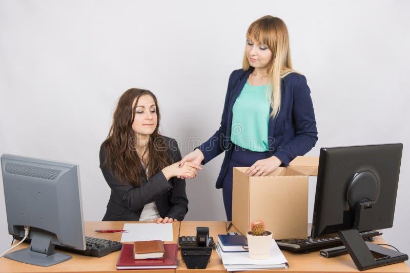 女孩在站立与在箱子前面的微笑的办公室和与同事握手 库存照片