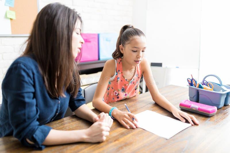 女孩在纸的读书教训由私人教师在表上 免版税库存图片