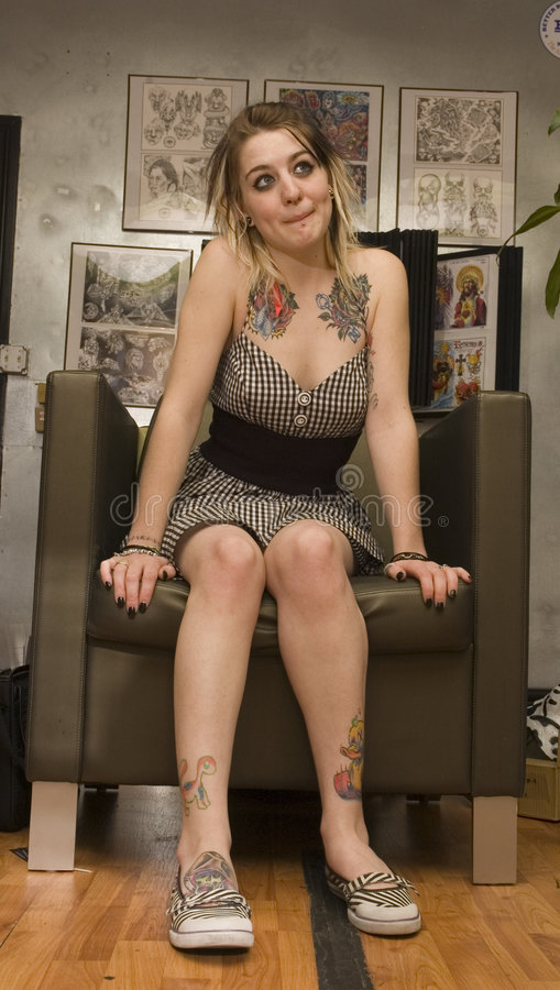 女孩在纹身花刺客厅里 库存照片