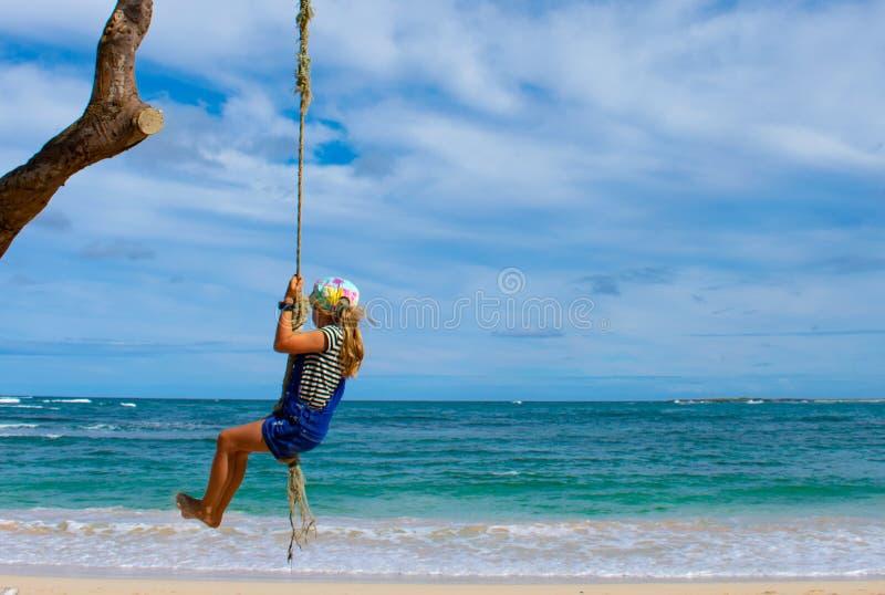 女孩在绳索摇摆摇摆由海滩 免版税库存图片