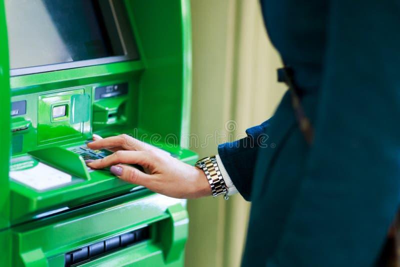 女孩在绿色现金分送器的采摘pincode的图象 免版税库存图片