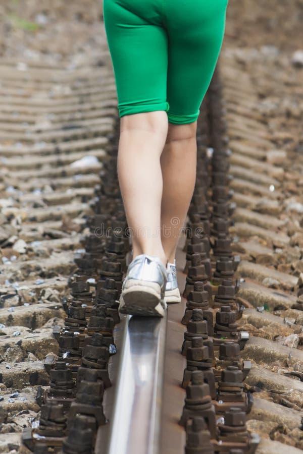 女孩在老被放弃的路轨走 免版税库存图片