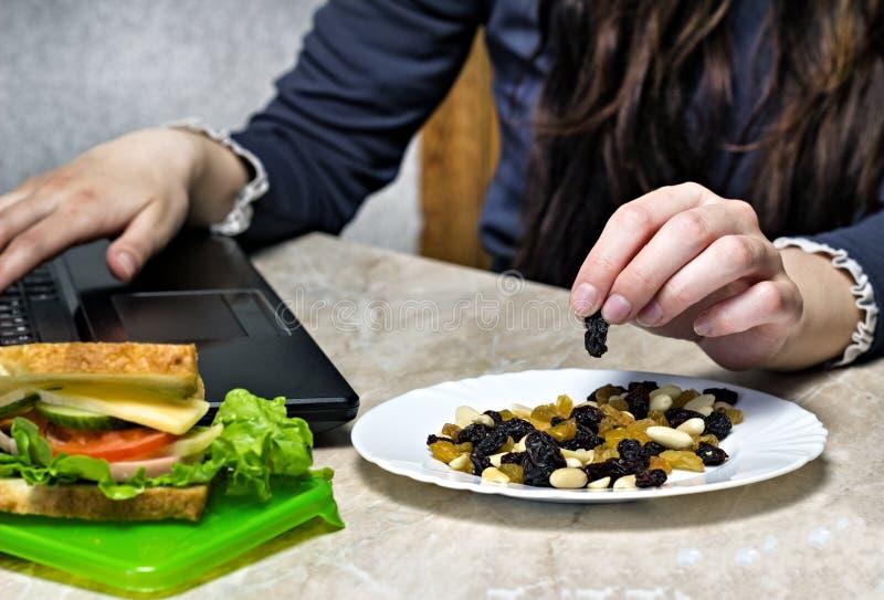 女孩在膝上型计算机后工作并且从板材干果子,三明治,一顿快餐采取在工作,特写镜头 免版税库存照片