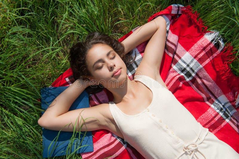 女孩在草的格子花呢披肩说谎 免版税图库摄影