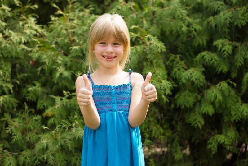 女孩在蓝色礼服的5岁显示拇指 库存照片
