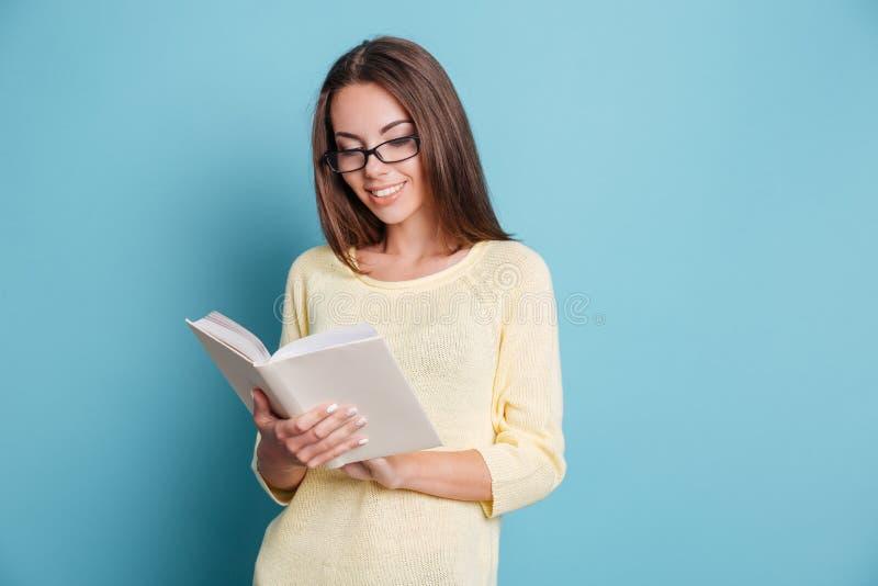 女孩在蓝色背景的阅读书 免版税库存图片