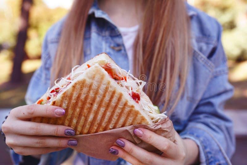 女孩在街上吃沙瓦玛 快餐 库存照片