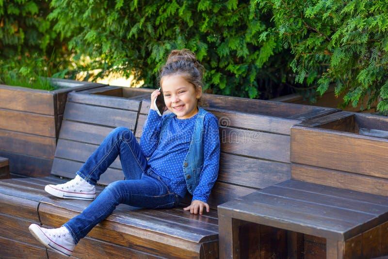 女孩在街道和微笑的电话谈话 W 免版税库存图片