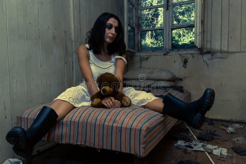女孩在被放弃的屋子里 免版税库存图片