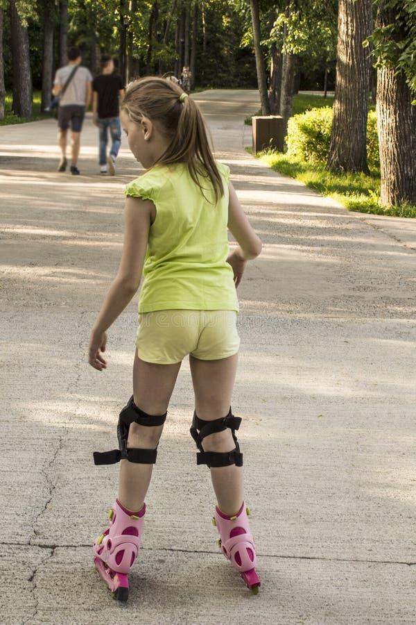 女孩在路辗滚动在公园 免版税库存照片
