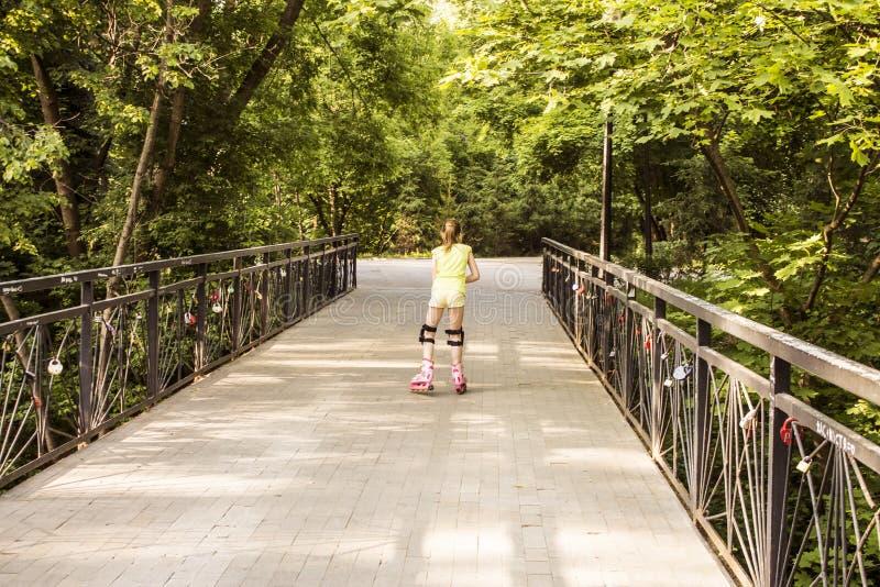 女孩在路辗滚动在公园 免版税图库摄影