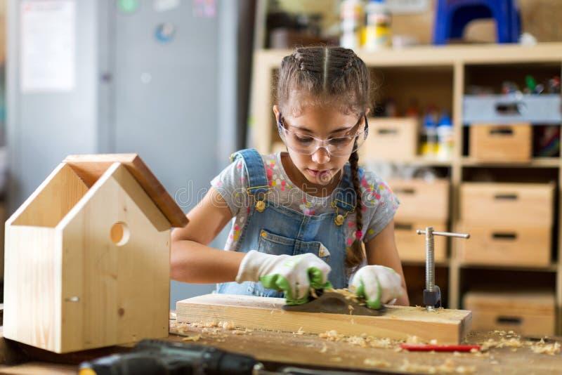 女孩在车库的大厦鸟舍 免版税图库摄影