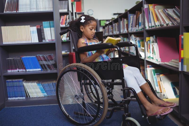 女孩在轮椅的阅读书在图书馆里 免版税库存照片