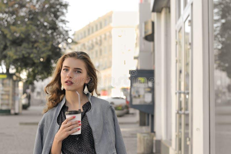 女孩在边路和饮用的咖啡去 免版税库存照片
