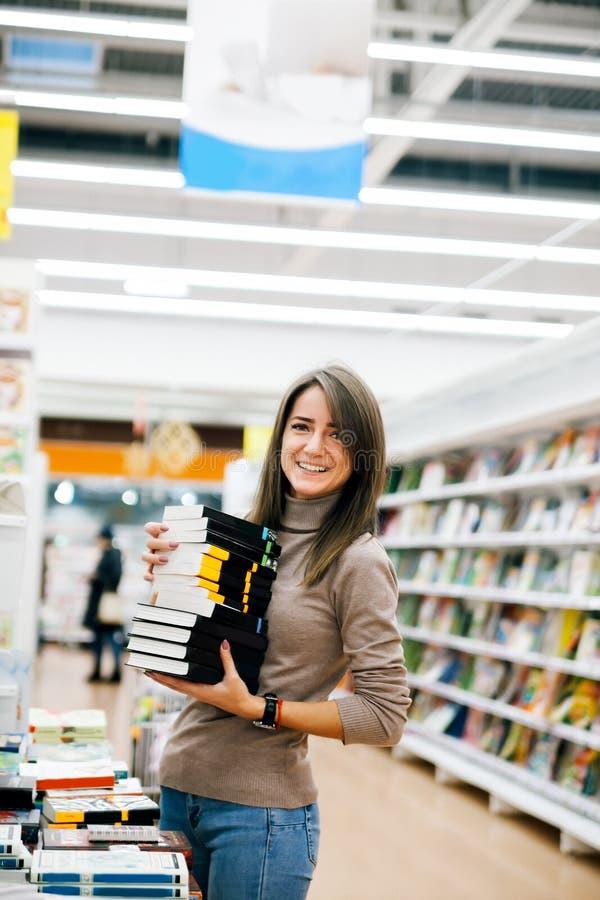 女孩在选择书的书店 免版税图库摄影