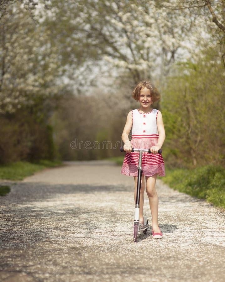 女孩在道路的骑马滑行车穿过公园 免版税图库摄影