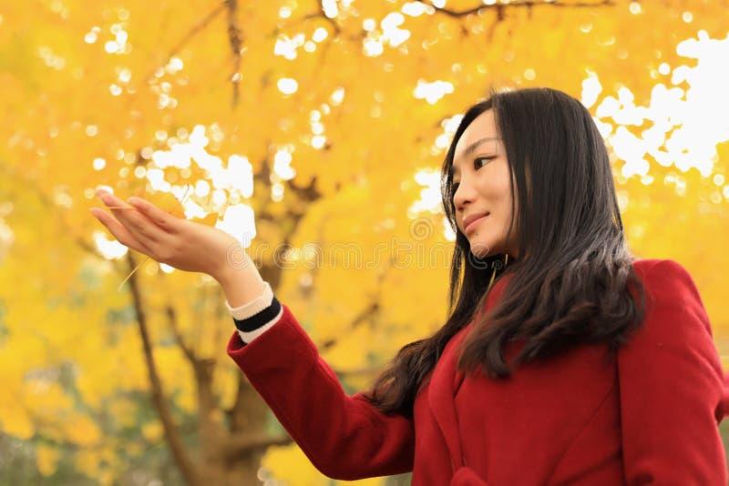 女孩在金黄秋天庭院里 图库摄影