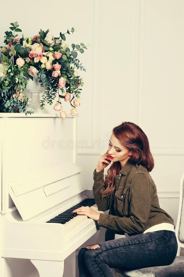女孩在钢琴旁边坐 免版税图库摄影