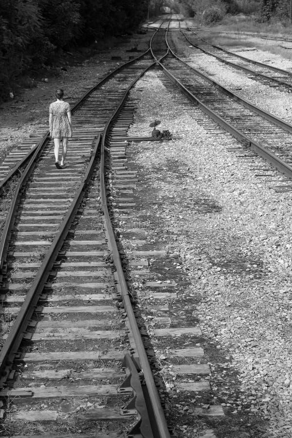 女孩在铁轨单独走,黑白 免版税库存照片