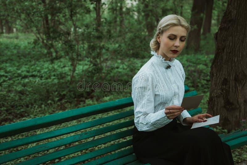 女孩在长凳读一封信在公园 图库摄影