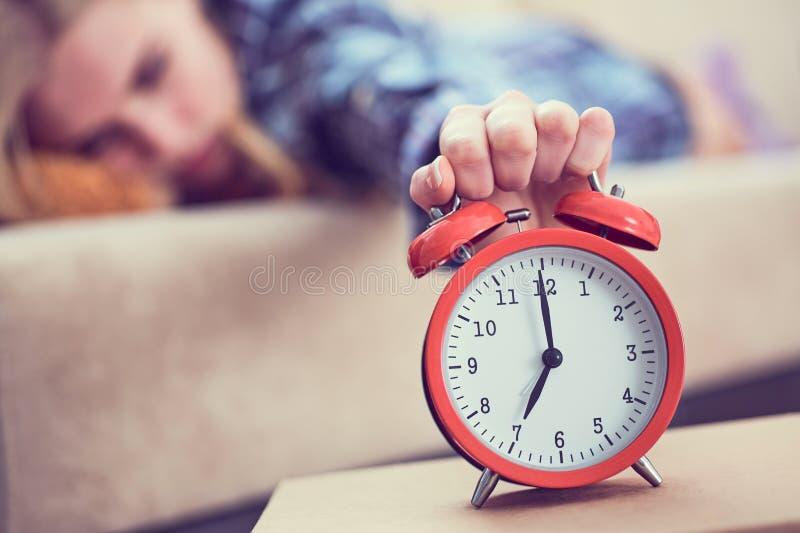 女孩在长沙发说谎并且伸她的手到红色闹钟关闭它 后醒 免版税库存图片