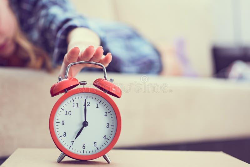 女孩在长沙发说谎并且伸她的手到红色闹钟关闭它 后醒 库存图片