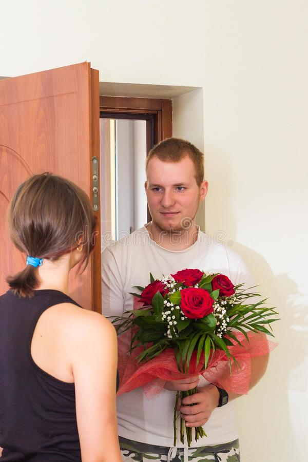 女孩在门附近遇见有花的男朋友 免版税图库摄影