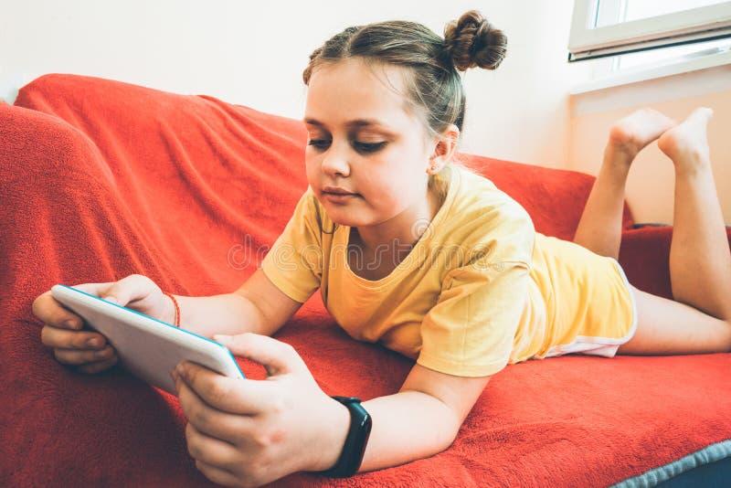 女孩在阳台的一个红色沙发说谎有片剂的 免版税库存图片