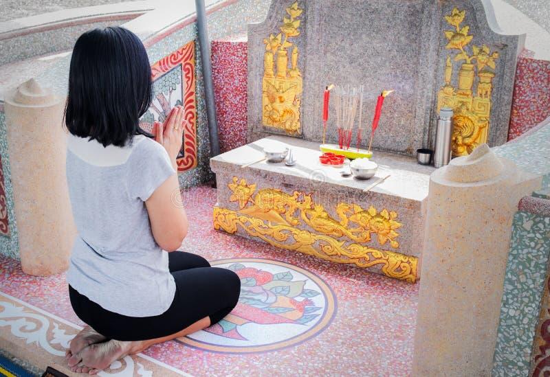 女孩在陈铭节日坐并且致以尊敬在她的家庭坟墓  免版税库存照片