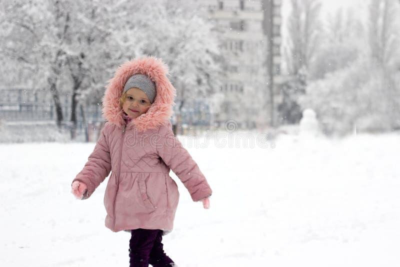 女孩在雪坐,取笑外面,在夜落的新鲜的雪 免版税库存图片