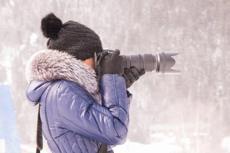 女孩在雪风暴的冬天拍摄了在与远摄镜头的一台SLR照相机 免版税库存照片