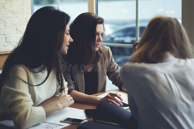 女孩在非正式会议期间的名牌服装在办公室使用现代技术和wifi 免版税库存照片