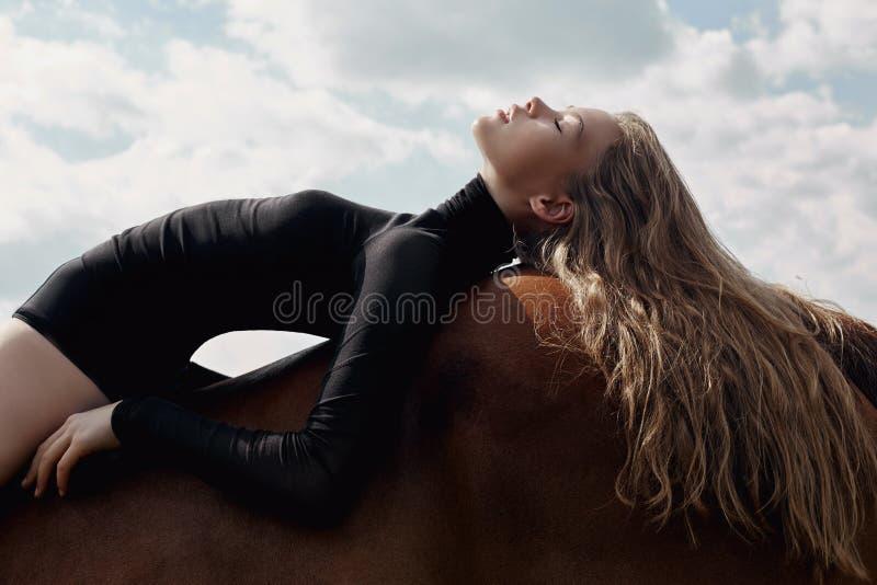 女孩在领域的一匹马弯曲的车手谎言 妇女的时尚画象和母马是马在天空的村庄 免版税库存图片