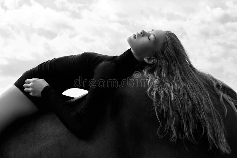 女孩在领域的一匹马弯曲的车手谎言 妇女的时尚画象和母马是马在天空的村庄 免版税图库摄影