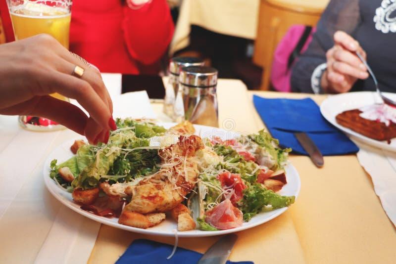 女孩在餐馆吃凯萨色拉 图库摄影