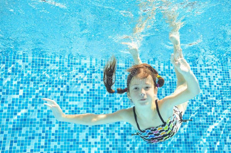 女孩在水下的水池跳,潜水并且游泳,愉快的活跃孩子获得乐趣在水下,孩子体育 免版税库存图片